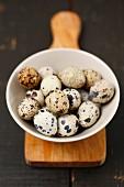 Quail eggs in a bowl on a chopping board