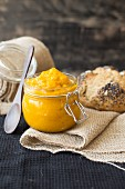 Pumpkin dip in a glass jar in front of a loaf of sour dough bread