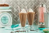Two chocolate milkshakes in a vintage setting
