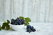 Fresh Concord grapes in a colander on a wooden surface