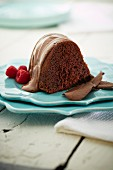 A slice of chocolate cake with chocolate icing and raspberries