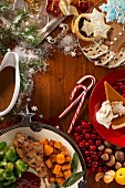 A Christmas meal with turkey, vegetables, gravy, pumpkin pie, gingerbread and biscuits (seen from above)