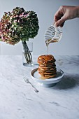 Maple syrup being poured onto a stack of vegan banana pancakes