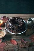 A carob and apple Bundt cake with chocolate ganache on a cake stand