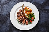A grilled beef rib steak on a white plate with potato wedges and tomato and rocket salad