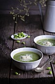 Creamy pea and broad bean with Parmesan in ceramic bowls on a wooden table