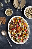 Cherry tomato salad and goats' cheese balls with toasted seeds served with white wine and bread