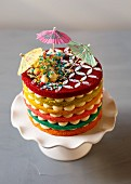 A rainbow cake with cocktail umbrellas