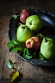 Red and green pears in a dish