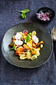 A summery pasta salad with peach, tomatoes and mozzarella