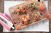 Vegan bruschetta with tomatoes and olives on a wooden board (seen from above)