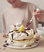 A meringue cake with pears and chocolate sauce