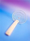 A Chinese fry sieve against a coloured background