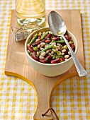Bean salad in a bowl on a wooden board