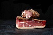 Tyrolean ham and bacon in front of a dark background