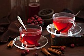 Two cups of hot cranberry tea with spices
