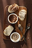 Vegan almond and coconut-almond spreads on bread and in little tubs