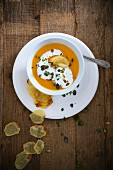 Vegan pumpkin soup with soya cream and potato chips
