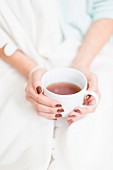 A woman's hands holding a cup of tea