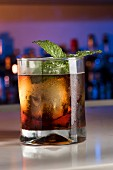 Aged rum cocktail with amaro, mint and ice cubes