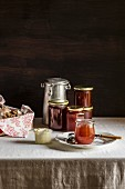 Glass jars with amber colored jam, butter jar and milk can on white table