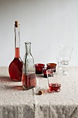 Rosé wine in bottles and a glass on a beige tablecloth