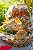Bundt cakes of various sizes in basket on table in summery meadow