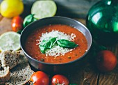 Tomato soup garnished with grated cheese and basil