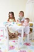 Drei Kleinkinder im Kinderzimmer mit weißem Kindertisch und Spielzeug