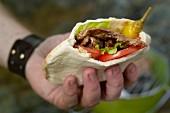 A hand holding a kebab