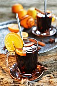 Mulled wine in two glasses with orange, cinnamon, star anise and cloves