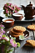Coconut cookies stacked on plate, tea and flowers in the background