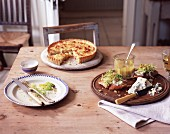 A quiche and slices of baguette topped with blue cheese and salad on a rustic wooden table