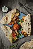 Tortilla wraps with spiced chicken, onion, peppers, salsa and a side serving of yoghurt dip