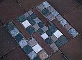 Mosaik aus verschiedenfarbigen kleinen Pflastersteinen