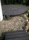 Kieselsteinpflaster zwischen Holzsteg UND