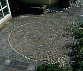 Innenhof mit Spirale aus PORPHYR UND Granitpflastersteinen