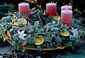 Adventskranz aus Hedera-Efeuzweigen, Orangenscheiben, Zimtstangen und Adventsker