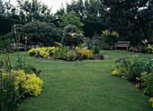 Sommergarten mit rundem Mittelbeet mit Teich und Stauden
