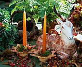 Herbstliche Dekoration mit Hirschfigur und Kerzen