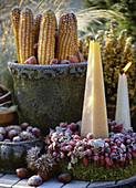 Kerze im Kranz aus Hagebutten und Moos, Topf mit Maiskolben