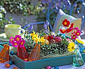 Tablett mit Buchskranz, gekochten Eiern, Vasen mit Blüten