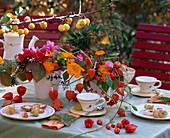 Tischdeko: Gesteck aus Rosa / Rosen, Calendula / Ringelblumen, Physalis / Lampionblume