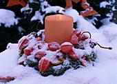 Kranz mit brennender Kerze im Schnee