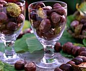Aesculus hippocastanum / Kastanien in Weingläsern und als Kette auf dem Tisch