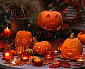Tisch mit ausgehöhlten, geschnitzten Kürbissen mit Gesichtern und Sternen, Kerze