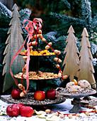Hölzerne Tannenbäume, Metalletagere als Vogelfutterstation mit Malus / Äpfel, Ar