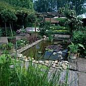 Rechteckiger Teich mit Nymphaea (Seerose), kleines Staudenbeet mit Heuchera (Purpurglöckchen), Rosa (Kletterrosen, Ramblerrosen) an Pergola, Staemmchen in Holzkuebeln, Blumenspindel mit Petunia (Petunien)