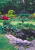 Teichbecken mit Nymphaea (Seerosen) und Sumpfpflanzen, Staudenbeet mit Acer shirasawanum 'Aureum' (Goldahorn), liegende Figur als Deko, hinten blühende Azaleen