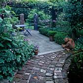 Schattige Terrasse unter Pergola, blaue Sitzgruppe, Gartentor, Buxus (Buchs), Terracotta-Figur